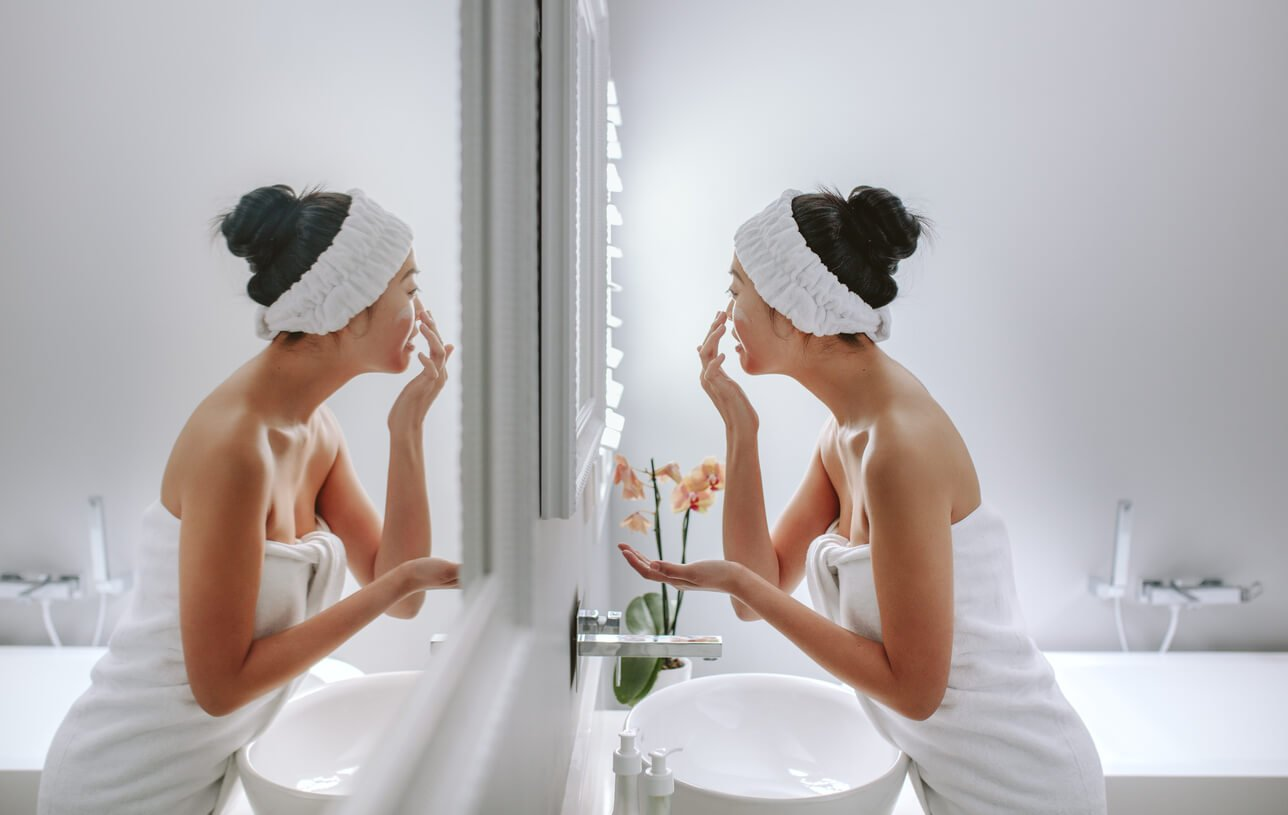 A woman doing her A.M skin care routine at home as recommended by SkinScience Clinic